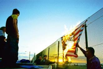 Protesters burn an American flag during a rally against the Free Trade Agreement of the Americas (FTAA) on the San Diego-Tijuana border in 2001. Photo: L. Matthew Bowler/Newsmakers